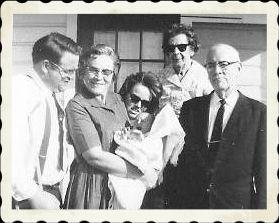 Dad, Grandma, Mom peaking head around Grandma, Me, Grandma R in background, Granddad.